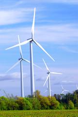 Wind power generators in the field against blue sky