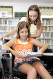 Two school girls reading notes in the library.   poster
