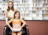 Two school girls at the library.  One is in a wheelchair. poster