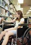 girl in a wheelchair selecting a book at the library. poster