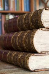 Three old books in front of library shelves