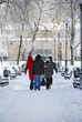 A family walking through the park in winter
