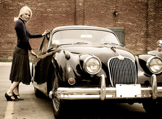 A beautiful blond woman getting into a classic car