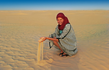 beautiful woman play sand in desert