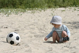 boy plays on sand with the toy automobile near to a football poster