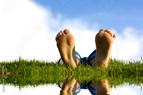 Feets on grass near water.