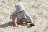 The boy on sand plays with the toy automobile poster