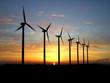 Wind turbine farm over sunset.