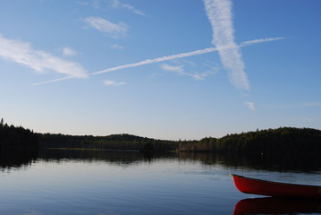 Red canoe reflects in lake in Algonquin Park at Sunset