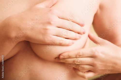 Woman examining her breast for signs of breast cancer