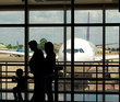 a family at an airport terminal with aeroplane in the background