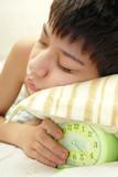 Deep sleep of the boy with green alarm-clock poster