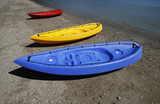 colorful kayaks on beach by turquoise waters poster