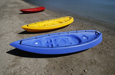 colorful kayaks on beach by turquoise waters