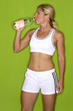 healthy athlete drinking water on green isolated background poster