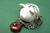 Piggy bank with a red combination lock and chain poster