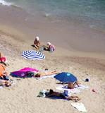 Baigneurs et parasols sur la palge à Cannes poster