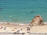 Baigneurs,parasols et rochers  sur la plage de Cannes poster