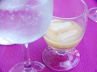 Apéritf anisé et verre d'eau sur nappe violette