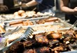 People around trays of juicy barbecue food - 3903405