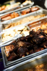 Trays of juicy barbecue food, focus on ribs in front