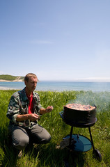 The man prepares for a barbecue from chicken on seacoast.