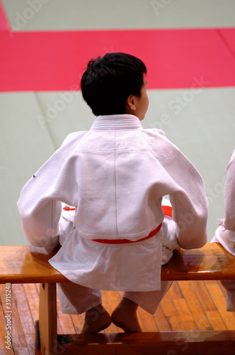 A karate kid sitting on bench and watching the competition