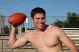 A shirtless man throwing a pass on the football field poster