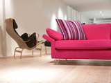 A pink sofa with pillows and an armchair on a pine wood floor poster