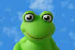 A green plastic toy-frog against a blue sky