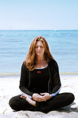 A woman in deep meditation at the beach