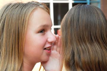 Two young teenage girls gossiping in school yard