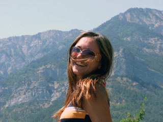 Portrait of the beautiful girl on a background of mountains