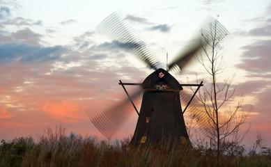 Windmills in Kinderdijk (Netherlands) at windy sunset.