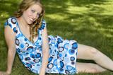 Cute blonde on grass, in a blue polka dot dress poster
