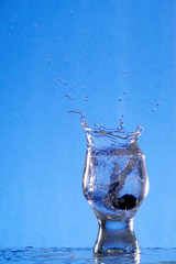 A glass with a drink splashing about