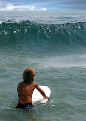 California boy on the beach ready for surfing