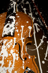 Old grunge violin spattered with white paint without strings in