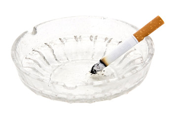 burning cigarette in glass ashtray