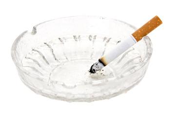 burning cigarette in glass ashtray