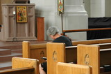 Man reading his bible in church alone. poster