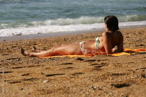 femme qui bronze sur la plage