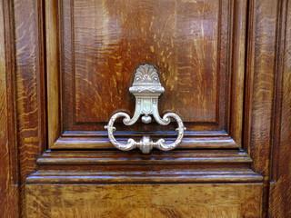 Porte en bois ouvragée avec poignée en bronze