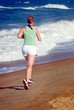 Photo of Young woman running alone on the beach.