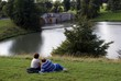 couple relaxing on grass in front of lake with a bridge