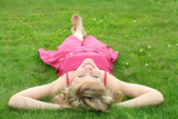 Fototapety Woman lying on grass, smiling