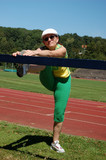 Active senior woman stretching in a stadium poster