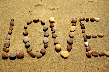 Love stone word in the sand