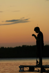 Child fishing on the pier at sunset