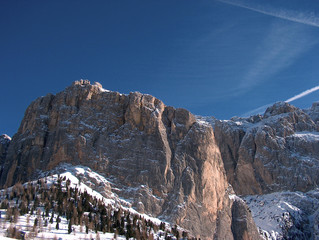 Rock mountains covered by snow and blue sky